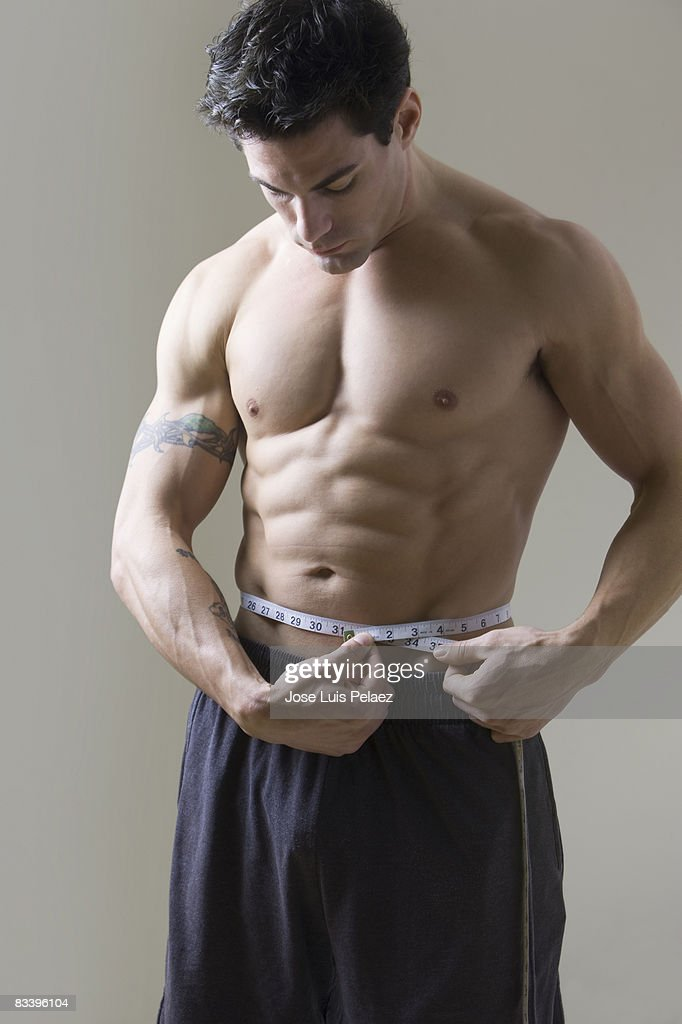 Young man measuring his waist : Stock Photo