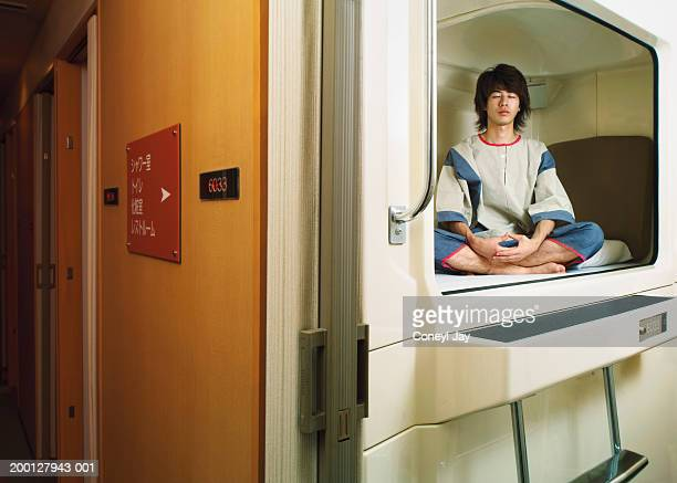 Young man meditating in capsule hotel (Digital Composite)