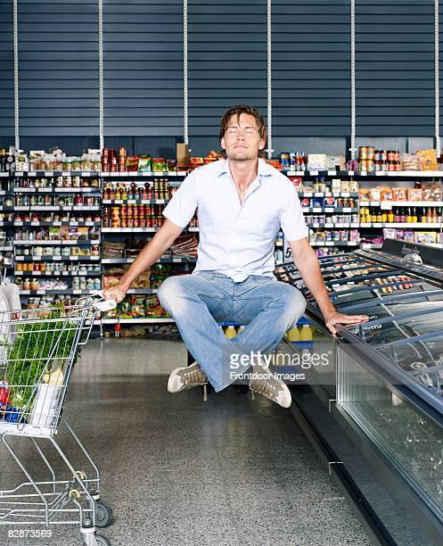 Young man meditating in supermarket, levitating.