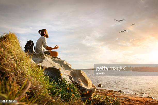 Young man meditating on the rock by sunset