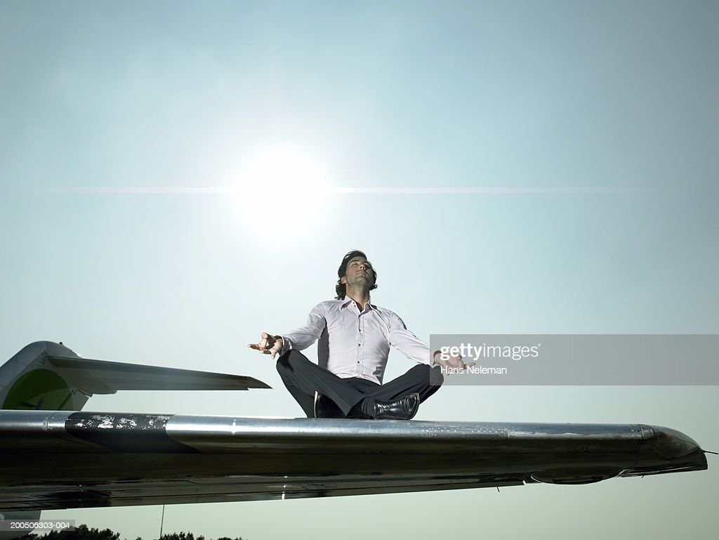 Young man meditating on wing of airplane : Stock Photo