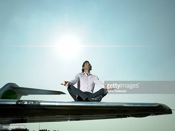 Young man meditating on wing of airplane