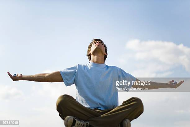 Young man meditating outdoors, holding yin yang balls in each hand