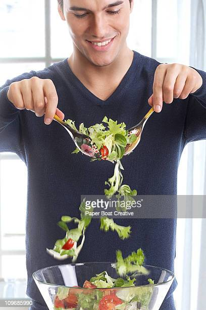 Young man mixing a bowl of fresh green salad