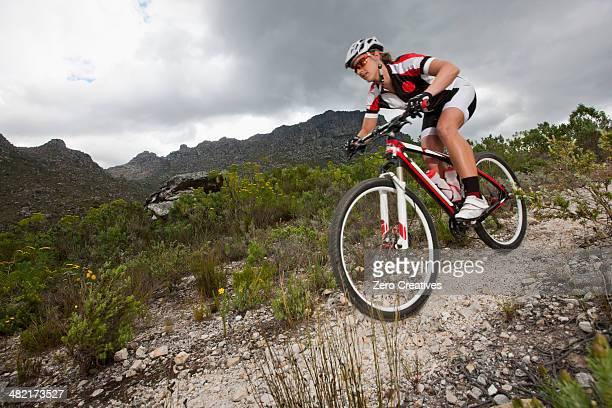 Young man mountain biking down mountain