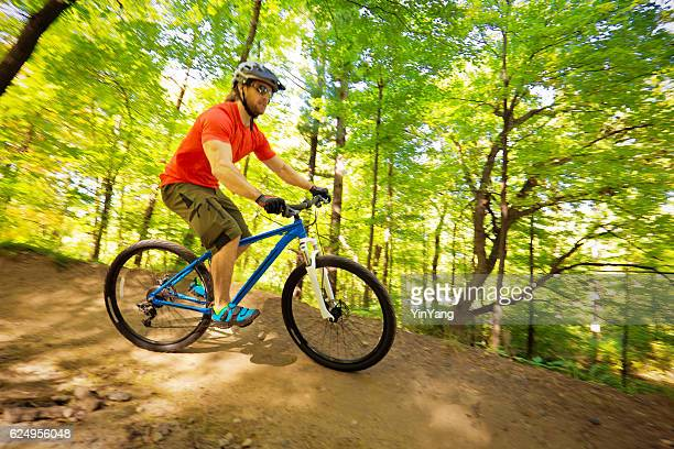 Young Man Mountain Biking in Forest Trail