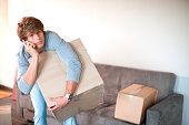 Young man moving house on cell phone carrying box