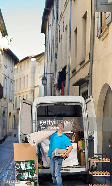 Young man moving in street with rug