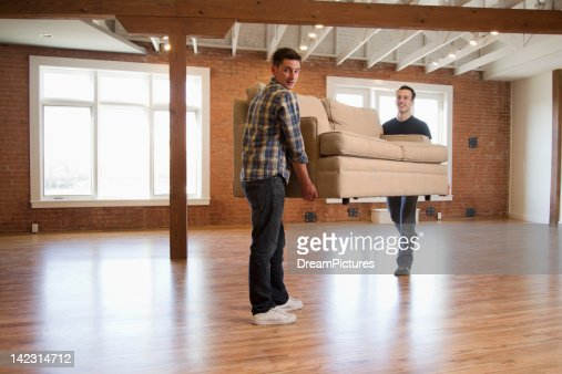 Young man moving into new loft apartment : Stock Photo