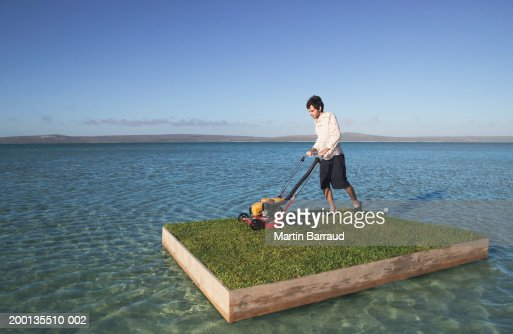 Young man mowing grass on raft at sea