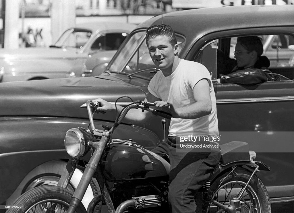 A young man on a motorcycle next to his buddy wearing a leather jacket in a car, San Francisco, California, mid 1950s.