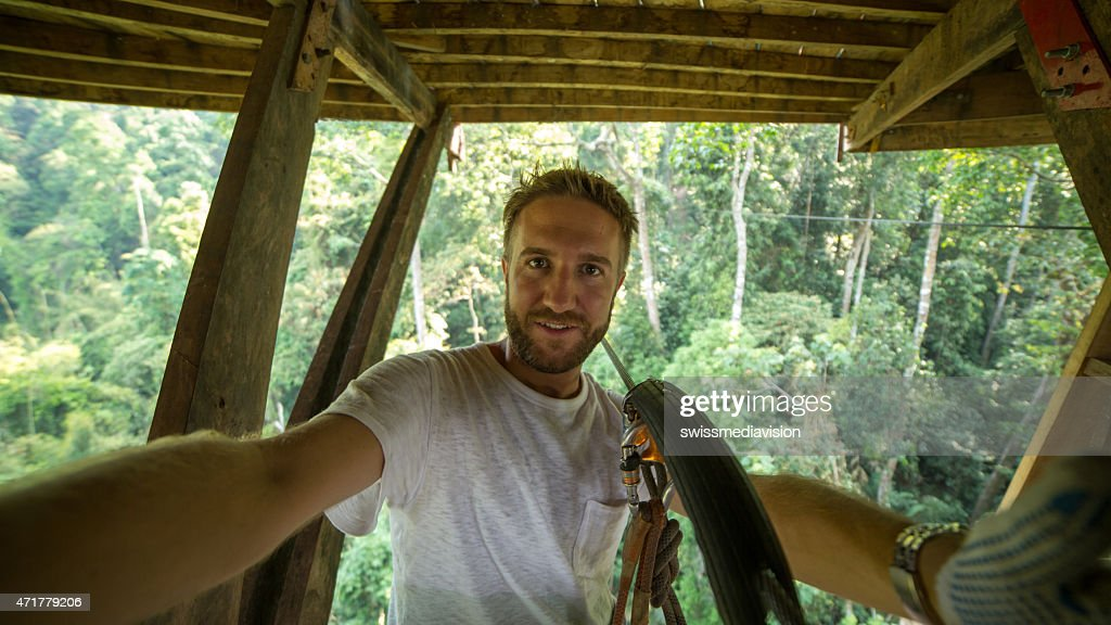 Young man on a zip-line adventure taking a selfie