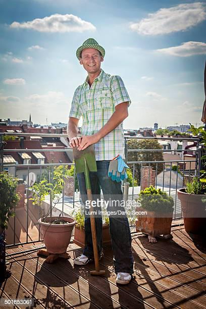 Young Man On Balcony Holding Shovel, Munich, Bavaria, Germany, Europe