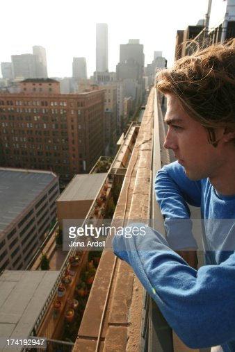 Young man on balcony overlooking city downtown stockfoto for Balcony overlooking city