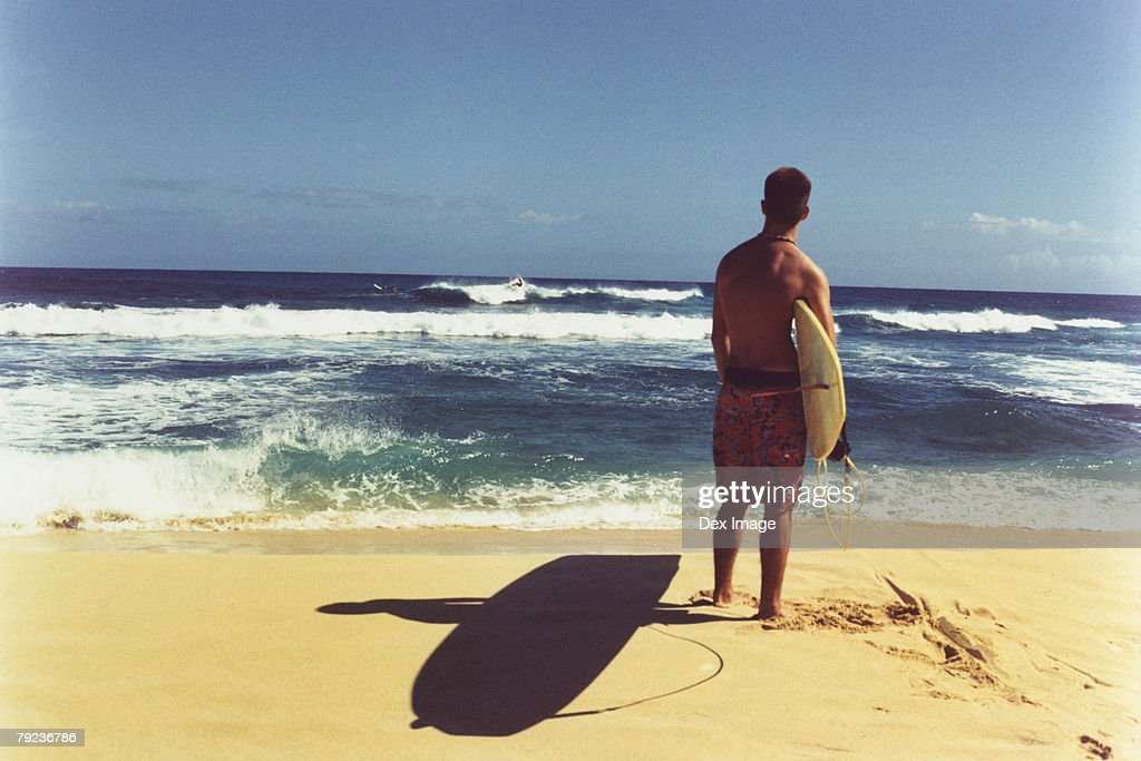Young man on beach holding surfboard, rear view : Stock Photo