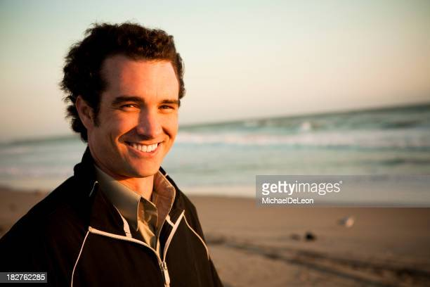 Young man on beach with coast in background