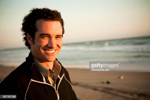 Hombre joven en la playa de la costa al fondo