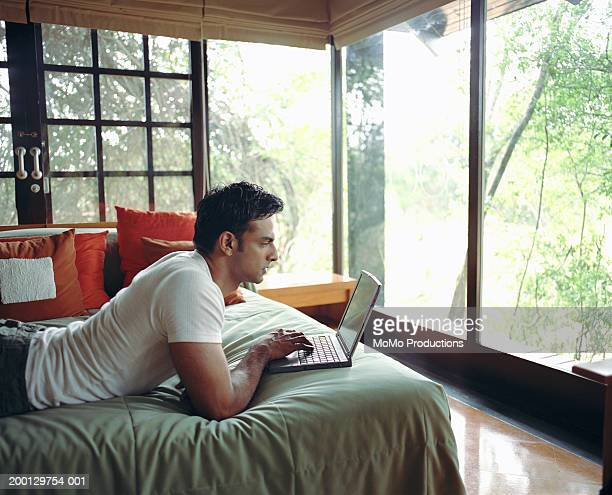 Young man on bed using laptop