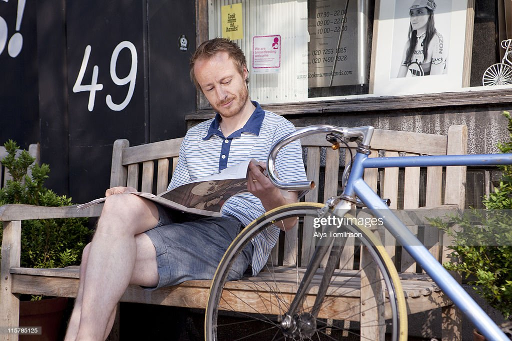 young man on bench reading newspaper, with bike : Stock-Foto
