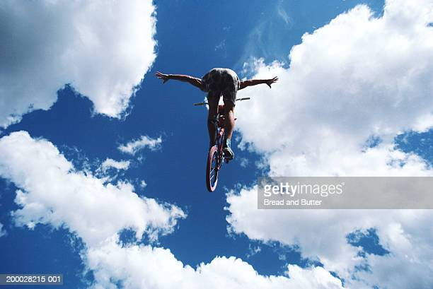 Young man on bike in mid air, low angle view
