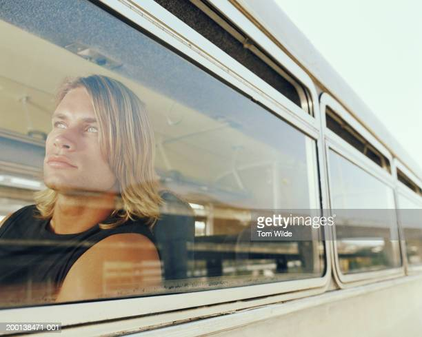 Young man on bus, view through window