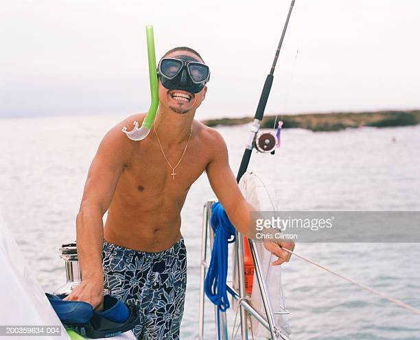 Young man on catamaran wearing snorkel