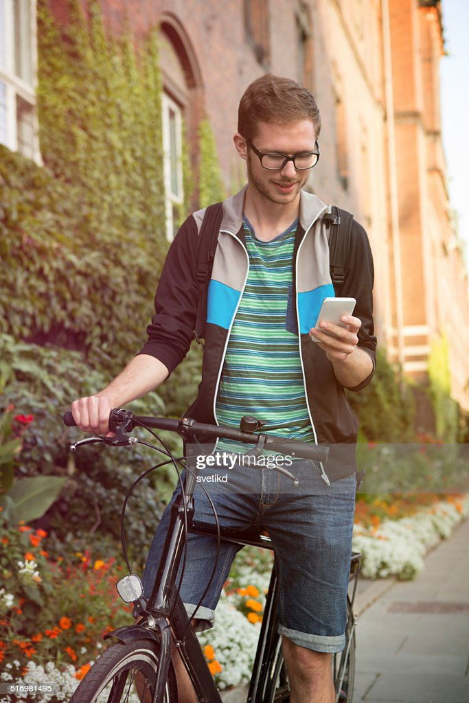 Young man on city street with bicycle.