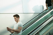 Young man on escalator using smartphone