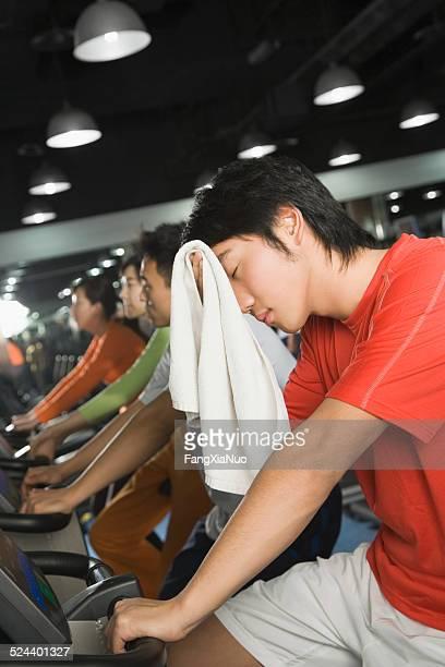 Jeune homme sur vélo d'exercice dans la salle de sport s'essuyer la transpiration