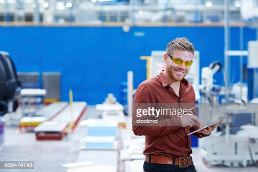Young man on factory shopfloor using digital tablet