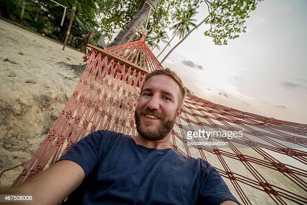 Young man on hammock taking selfie-Beach