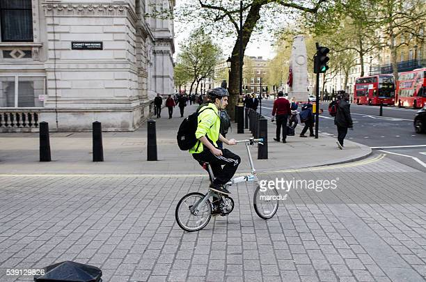 Young man on his foldable bicycle getting back home