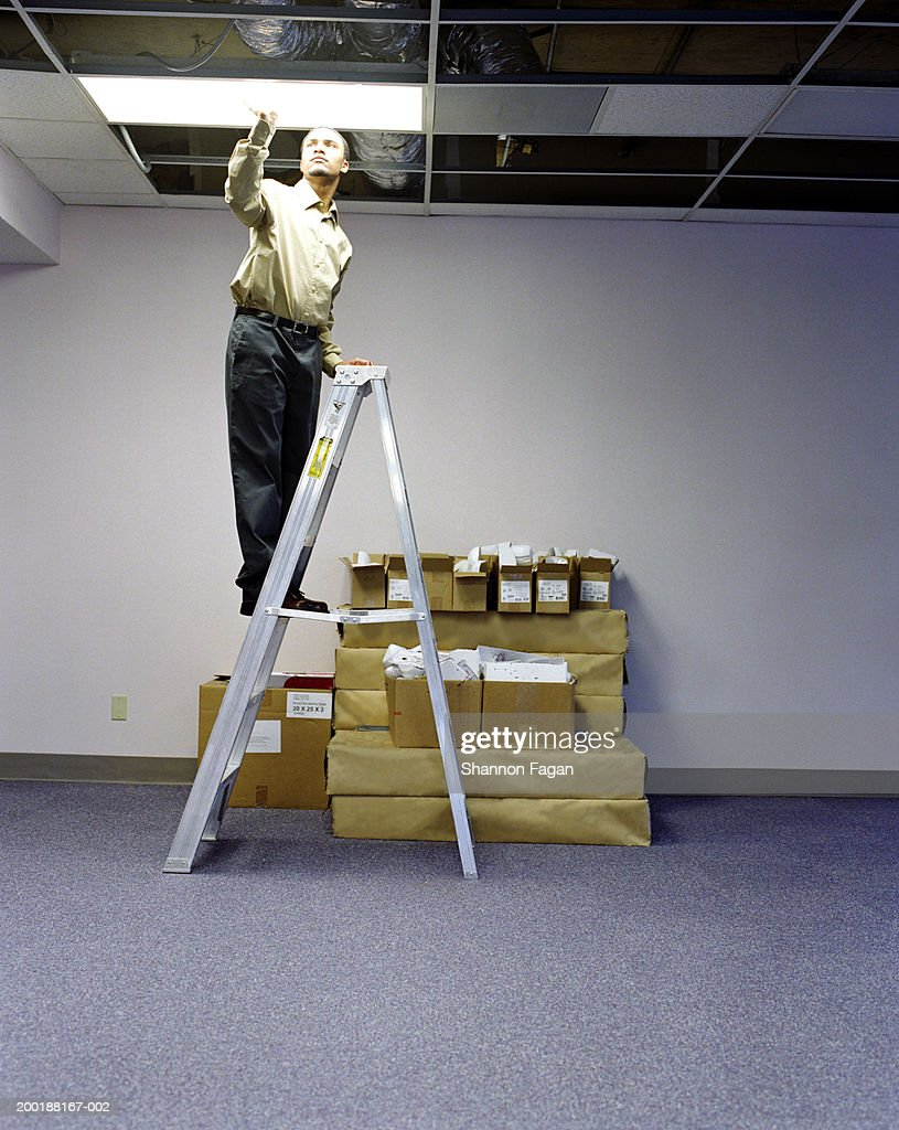 Young man on ladder installing ceiling light in empty office : Stock Photo