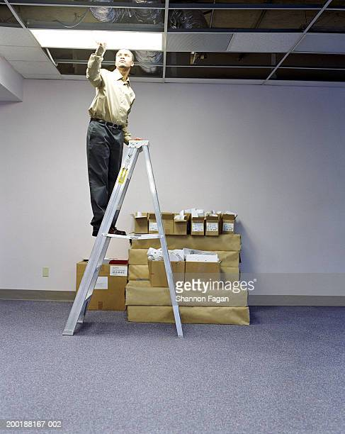 Young man on ladder installing ceiling light in empty office