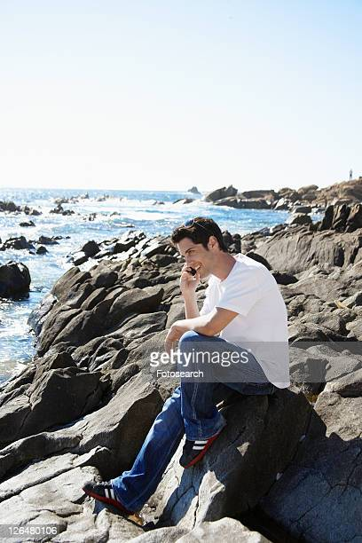 Young man on mobile phone by sea