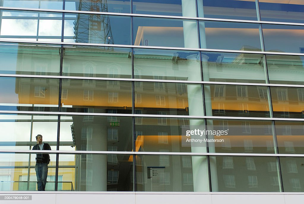 Young man on mobile phone, looking out of window : Stock Photo