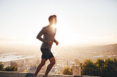 Young man training in the nature with sun behind him. Young man on morning run outdoors.