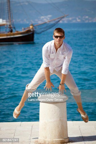 Young man on pier, jumping over bollard, Zadar, Croatia