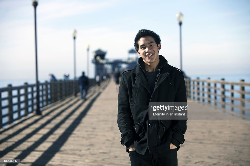 Young man on pier smiling to camera : Stock Photo