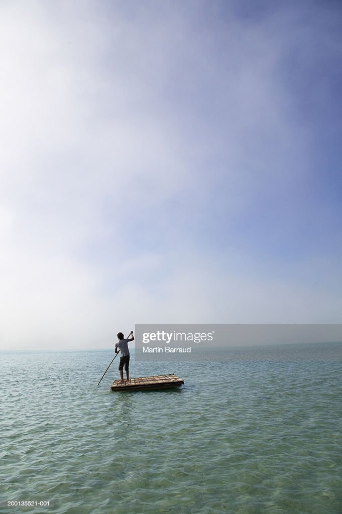 Young man on raft at sea, rear view : Stock Photo