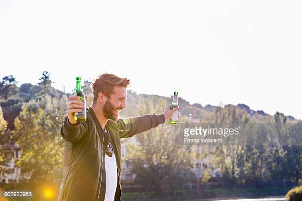Young man on riverbank with beer bottle
