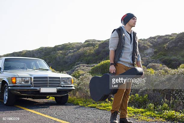 Young man on roadside with guitar case, Cape Town, Western Cape, South Africa