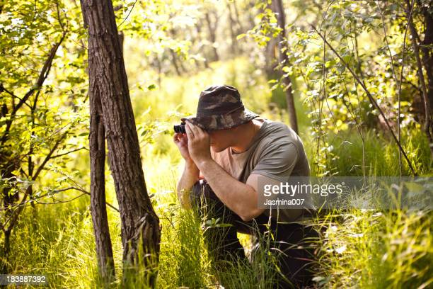Young man on safari holding binoculars