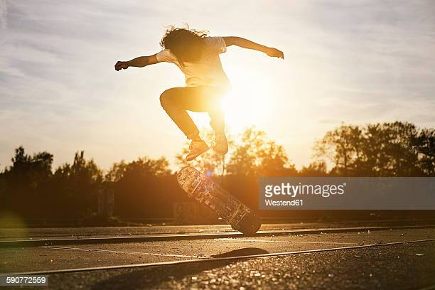 Young man on skateboard in backlight