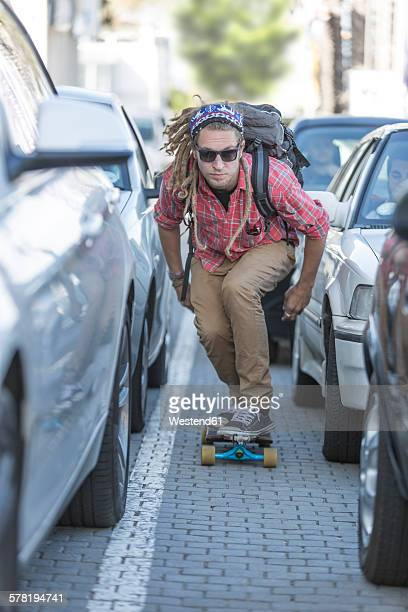 Young man on skateboard in traffic jam