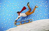 Happy young man on sled having fun against the blue background with snowflakes