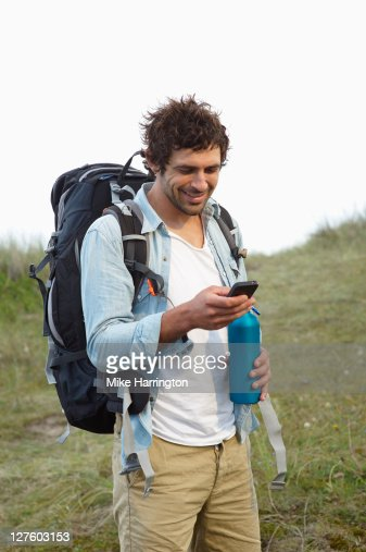 Young man on smart phone whilst hiking in dunes : Stock Photo