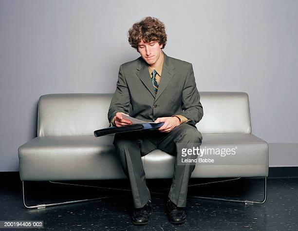 Young man on sofa looking at paperwork