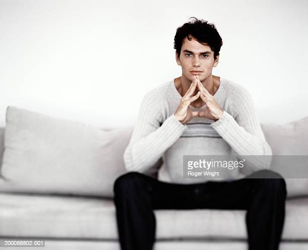 Young man on sofa, pressing hands together, portrait