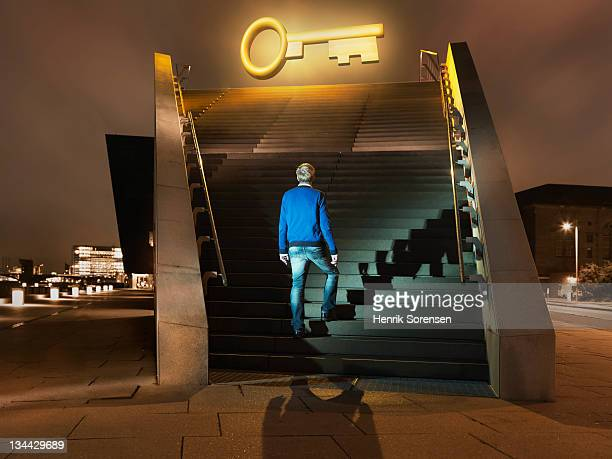 young man on stairs looking up at giant key